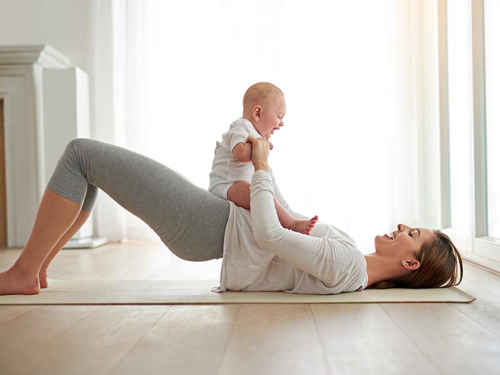 post pregnancy women with baby doing glute bridge